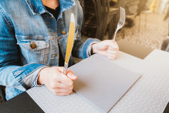 Hungry woman holding knife and fork, waiting for food, food or restaurant concept, warm light tone Royalty Free Stock Photos