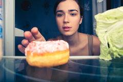 Hungry woman reaches for donut at night near fridge. Hungry woman near fridge at night with donut stock photo