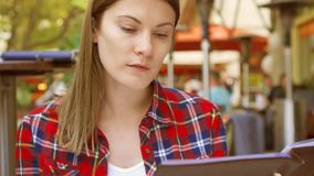 Hungry woman sitting in cafe looking at menu. Smiling beautiful female choosing food at restaurant stock footage