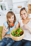 Hungry women eating a salad in the living-room Royalty Free Stock Photos