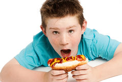 Hungry young boy eating a hotdog. Young boy with spikey hair eating a big hotdog covered in tomatoe ketchup and mustard. Isolated on a white background Royalty Free Stock Images