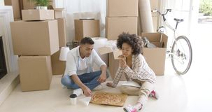 Hungry young couple eating a pizza on the floor stock footage