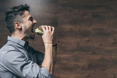 Hungry young man biting delicious hamburger. Side view of hungry young man biting delicious hamburger Stock Photo