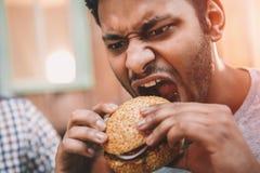 Hungry young man biting gourmet homemade hamburger royalty free stock photos