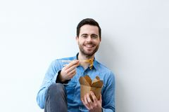 Hungry young man smiling with chopsticks Royalty Free Stock Photo