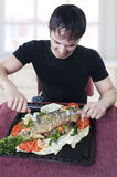 Hungry young man waiting to eat. Freshly roasted stuffed fish with two forks on light kitchen at home Stock Images