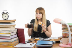 Hungry young teacher sitting wearily with a sandwich and coffee Royalty Free Stock Photo