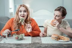 Hungry young woman biting piece of burger royalty free stock image