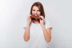 Hungry young woman eating chocolate stock photos