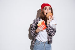 Hungry young woman eating fries and burger Royalty Free Stock Photography