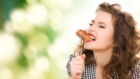 Hungry young woman eating meat on fork over green. People, diet and food concept - hungry young woman eating meat on fork over green natural background stock photos