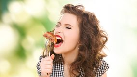 Hungry young woman eating meat on fork over green. People, diet and food concept - hungry young woman eating meat on fork over green natural background stock photography