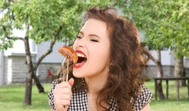 Hungry young woman eating meat on fork over house. People, diet and food concept - hungry young woman eating meat on fork over house and summer garden background royalty free stock photography