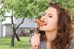 Hungry young woman eating meat on fork over house. People, diet and food concept - hungry young woman eating meat on fork over house and summer garden background royalty free stock images