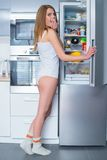 Hungry young woman snacking out of the fridge Royalty Free Stock Photography