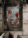 Hungry zombie at the window. Photo of a hungry zombie staring at you through a dirty window stock photo