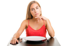 Hungy Woman Waiting With An Empty Plate. Hungry woman on a diet waiting with an empty place, isolated in white Stock Photo