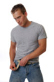 Hunk. A handsome muscular man tugging on his belt stock photos