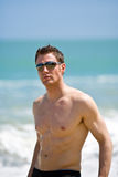 Hunk at the beach with shades. Young handsome Caucasian man with sunglasses Stock Photos