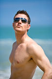 Hunk at the beach with shades. Young handsome Caucasian man with sunglasses Royalty Free Stock Photography