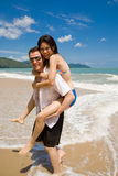 Hunk carrying woman piggyback. Caucasian hunk carrying a gorgeous Asian woman on his back having lots of fun Stock Images