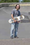 Hunk posing with his skateboard. A skateboarder hunk posing with his board Royalty Free Stock Image