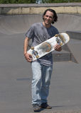 Hunk posing with his skateboard. A skateboarder hunk posing with his board Stock Images