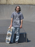Hunk posing with his skateboard. Sturdy skateboarder posing with his board in the skatepark Royalty Free Stock Images