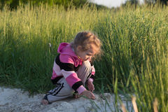 Hunkering little girl playing in field dirt outdoors at natural green meadow grass backdrop Royalty Free Stock Photos