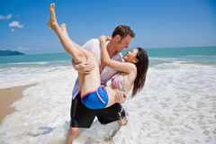 Hunky caucasian man carrying g. Strong handsome caucasian man carrying a beautiful asian girl at the beach Stock Image