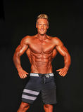 Hunky Male Bodybuilder Strikes a Pose. Handsome, hunky Chris Rueckert poses in the Men's Physique finals of the 2016 NPC Universe held in Teaneck, New Stock Photos