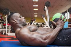 Hunky muscular black bodybuilder working out in Stock Image