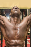 Hunky muscular black bodybuilder working out in Stock Photos