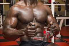 Hunky muscular black bodybuilder working out in Stock Photo