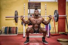 Hunky spier zwarte bodybuilder die binnen uitwerken royalty-vrije stock fotografie