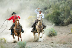 On the Hunt. Two Cowboys galloping and roping through the desert Stock Photo