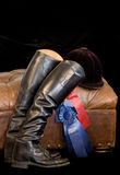 Hunt boots. English field style hunt boots, hunt cap and show ribbons resting against leather ottoman stock images