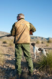 Hunter. Quail hunter in camouflage clothing walking across the field Royalty Free Stock Images