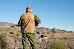 Hunter. Quail hunter in camouflage clothing walking across the field Stock Image