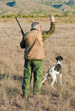 Hunter. Quail hunter in camouflage clothing walking across the field Stock Images