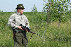 Hunter. With rifle standing in field Royalty Free Stock Photography