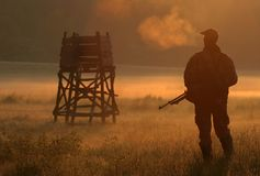 Hunter. Holds his gun in dawn Stock Photography