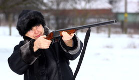 Hunter. Female hunter aiming with shotgun during winter season stock photography