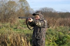 The hunter. The girl in a camouflage aiming from a gun Stock Image