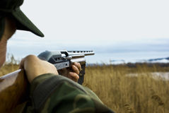 Hunter aiming. Senior hunter aiming towards a field, in a hunting party. Focus on the man's rifle stock photo