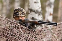 Hunter aiming from behind camouflage netting Royalty Free Stock Photos