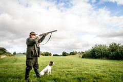 Hunter aiming. Hunter with dog aiming with his rifle Stock Photo