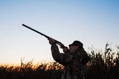 Hunter aiming at ducks at sunset Stock Photography