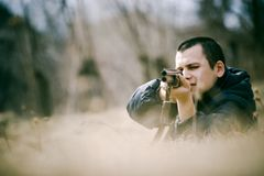 Hunter Aiming Gun. Crouching hunter aiming a shotgun Stock Photography