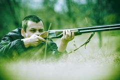 Hunter aiming Shotgun. Hunter aiming a shotgun.  Gun raised to face Royalty Free Stock Photography